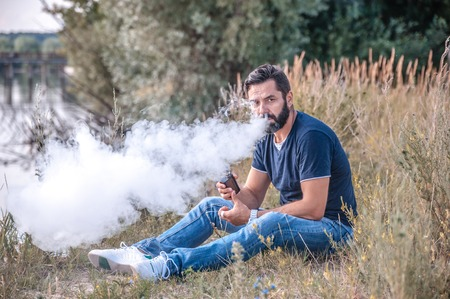 A man in the fresh air Smoking an electronic cigarette and looking at the camera