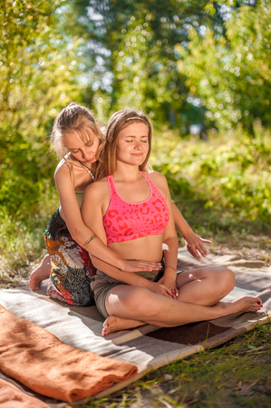 Massage expert gives her client a refreshing massage in nature.