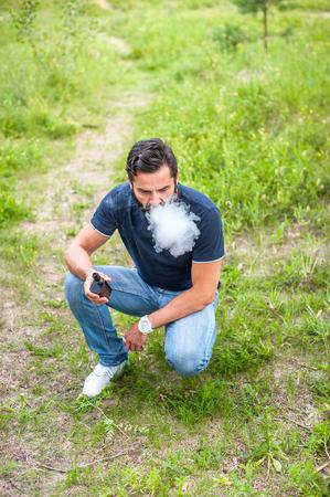 Brutal vaper enjoying e-cigarette in the daylight. Getting rid of nicotine addiction.