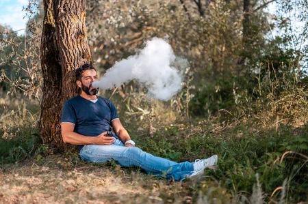 Handsome smoker enjoying an e-cigarette. Electronic cigarette. Stockfoto