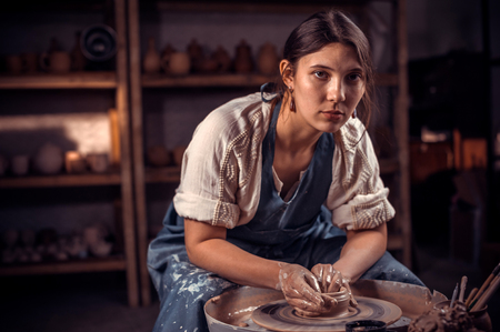 Charming pottery master shows how to work with clay and pottery wheel. Handicraft production.