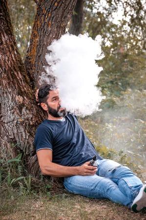 Bearded vape man blows up a couple an vape in the woods. Hybrid cigarette.