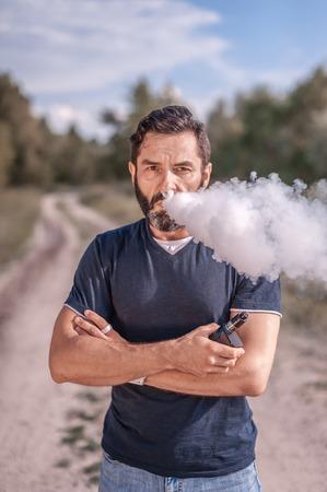Confident vaper enjoying electronic cigarette outside. Man really likes process of smoking.