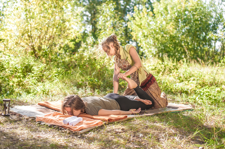 Massage expert performs a relaxing massage in a forest clearing.