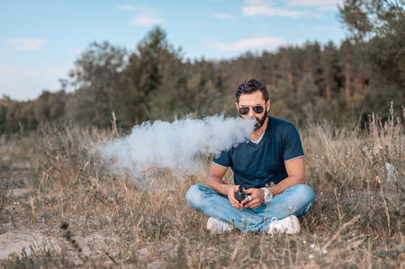 Stylish vape man enjoying an electronic smoke device outside. Vaping concept.