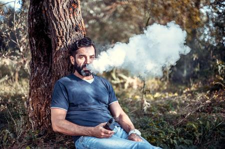 Handsome vaper enjoying an electronic cigarette. Man really likes process of smoking.