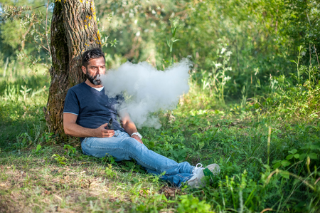 Modern man enjoying an electronic smoke device out in the forest. Electronic cigarette as alternative to tobacco. Stockfoto