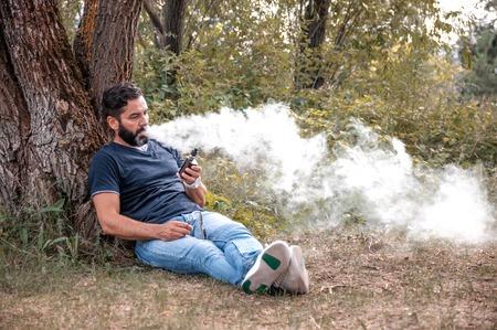 Confident smoker smokes electronic cigarette exhales smoke. Smoking cessation tobacco.