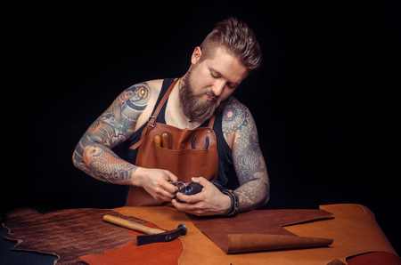 Professional Tanner works with leather goods at his workshop Stockfoto