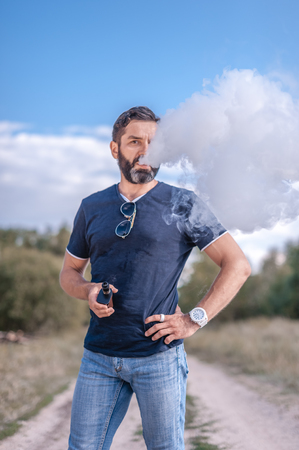 Confident vape man blowing a lot of smoke using vape vape. Vaping concept. Reklamní fotografie - 123624560