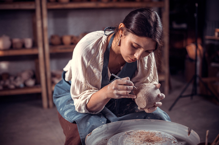 Charming ceramist girl is working on pottery wheel. Handmade. Reklamní fotografie
