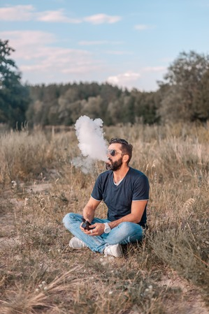 Handsome vaper smoking an electronic smoke device in a forest clearing. Electronic cigarette as alternative to tobacco. Reklamní fotografie