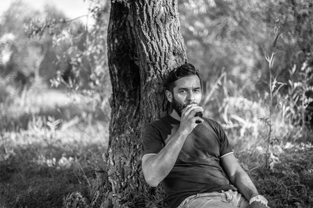Modern man enjoying e-cigarette in a forest clearing. Vaping.