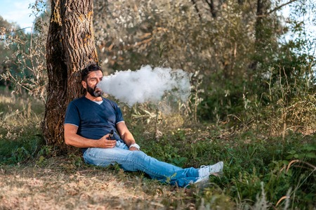 Bearded man blows up a couple an electronic cigarette on the forest ground. Getting rid of nicotine addiction.