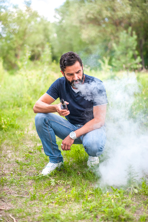 Stylish bearded smoker enjoying electronic smoke device. Electronic cigarette concept.
