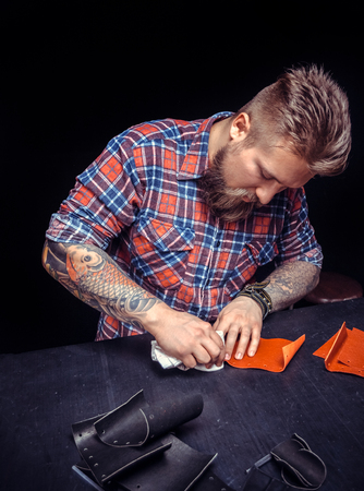 Leather Currier performing leatherwork on a new product piece at his workplace Reklamní fotografie