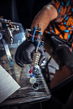 Hand of tattooer and a tattoo machine.