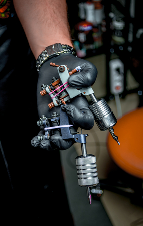 Hand of tattoo master and a tattoo machine.