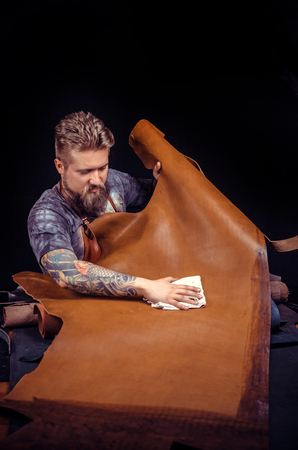 Tanner of leather keen on ones business at workshop