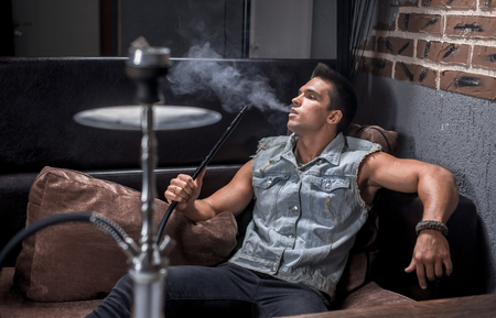 Sexy guy relaxes in a hookah in the shisha bar.