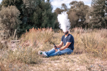 Stylish smoker enjoying an electronic cigarette out in the forest. The man smokes.