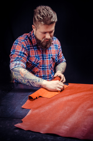 Man working with leather manufactures new product made of leather