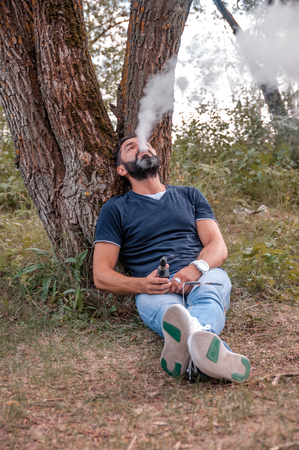 Modern vaper enjoying an electronic cigarette in nature. Electronic cigarette concept.