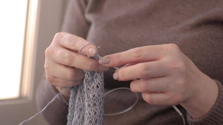 Close-up of hands knitting. A woman knits a sweater
