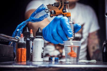 Hand of a tattoo artist with a tattoo gun.