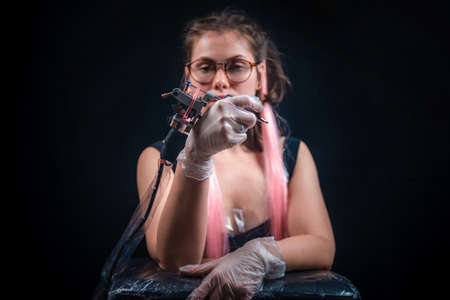 Tattoo artist with a tattoo-machine in tatoo salon