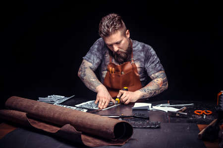Artist working with leather produces leather workpiece at the workplace