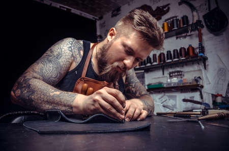 Leather cutter creates a new leather product at the tanner shop