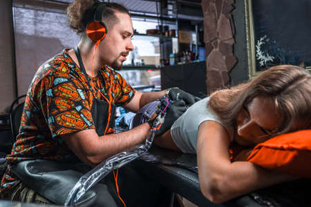 Tattoo master makes tattoo pictures in studio Stock Photo