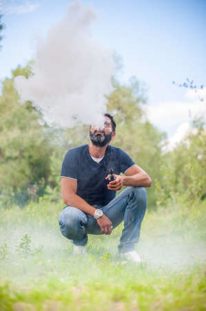 Stylish brutal man blows up a couple an electronic cigarette. Electronic cigarette as alternative to tobacco.
