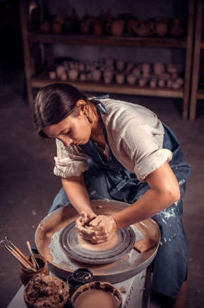 Charming ceramist woman sculpts from clay. Artisan production.
