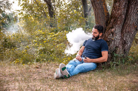 Bearded smoker blows up a couple an e-cigarette in nature. Handsome man.