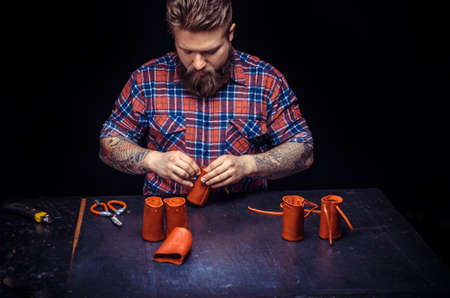 Tanner of leather cutting out leather goods in his leather studio Stockfoto