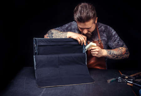 Professional Leather Worker performing leatherwork on a new product piece at the desk