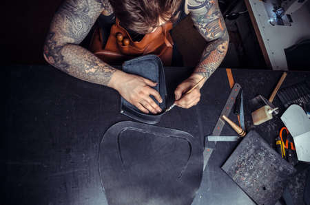 Artisan working with leather working with leatherwork at his workshelf