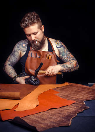 Leather Currier cuts out leather goods at his tanner shop