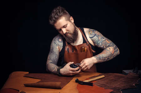 Tanner of leather produces leather goods at the studio Reklamní fotografie