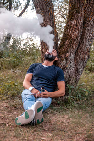 Stylish vaper in the fresh air smoking an electronic cigarette. Vaping activity.