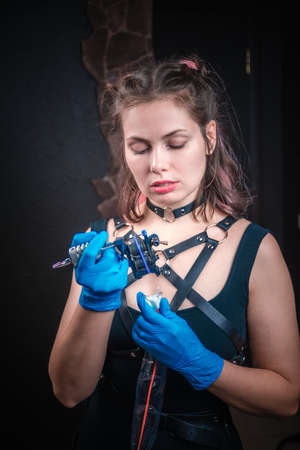 Tattoo artist poses for the camera in tattoo parlor