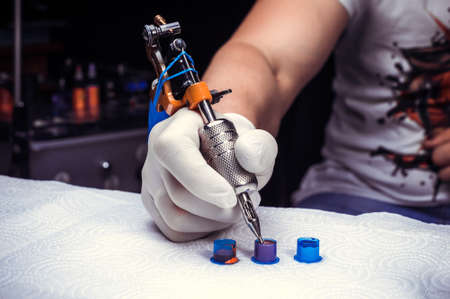 Hand of a tattoo master and a tattoo machine.