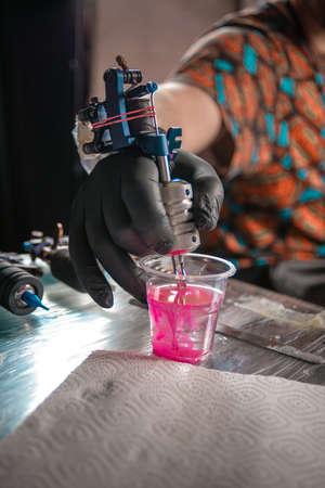 Hand of tattooer and a tattoo machine.