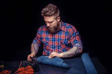 Tanner demostrating leather cutting process at his tanning shop Reklamní fotografie