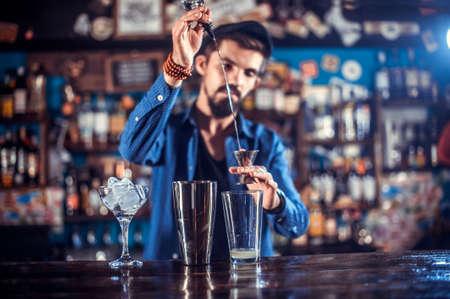 Barman formulates a cocktail behind the bar