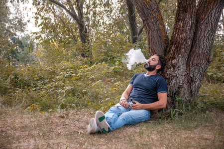 Handsome vape man blows up a couple an electronic cigarette. Modern ways of quitting tobacco.