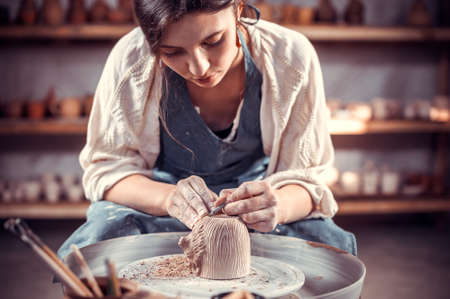 Master-ceramist creates a clay pot on a potters wheel. Hands of potter close up. Ancient craft and pottery handmade work