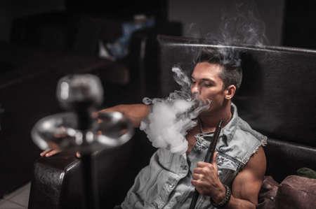 Young handsome man smoking shisha in the shisha bar.
